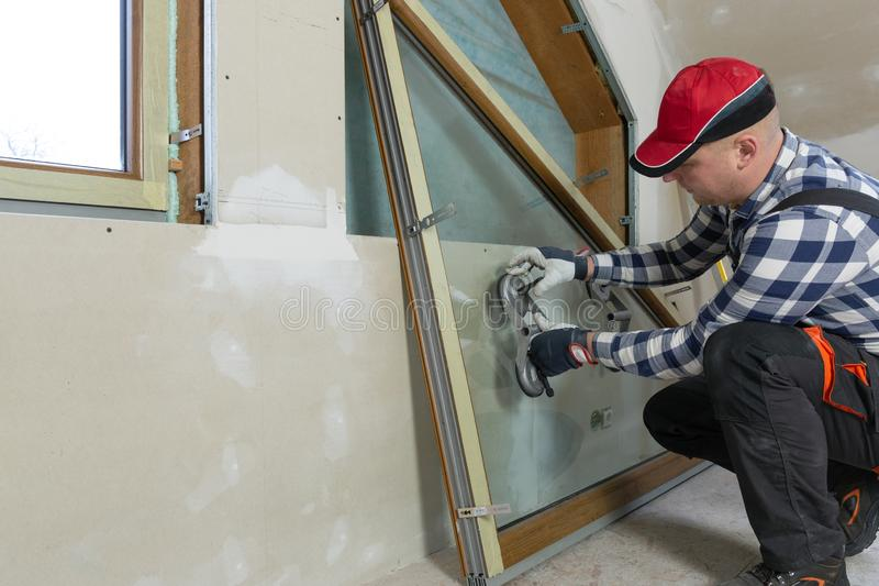 Handyman, construction man installing PVC window in a new insulated and filled dry wall attic stock photo