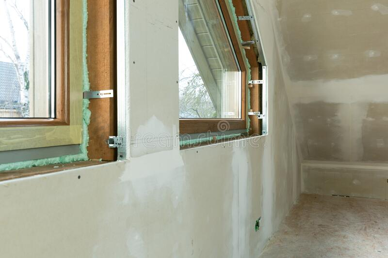 Handyman, construction man installing PVC window in a new insulated and filled dry wall attic stock photography