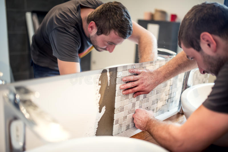 Handyman fixing and applying ceramic tiles on bathroom walls. royalty free stock photos
