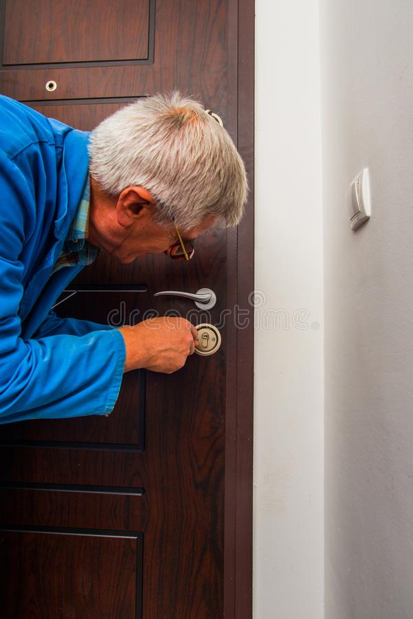 Handyman fixing door lock stock images