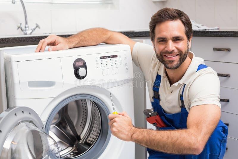 Handyman fixing a washing machine royalty free stock photography