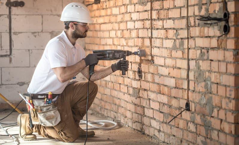 Handyman gebruikt een colberhammer, voor installatie, professionele werknemer op de bouwplaats Het concept elektricien en handyma royalty-vrije stock foto's