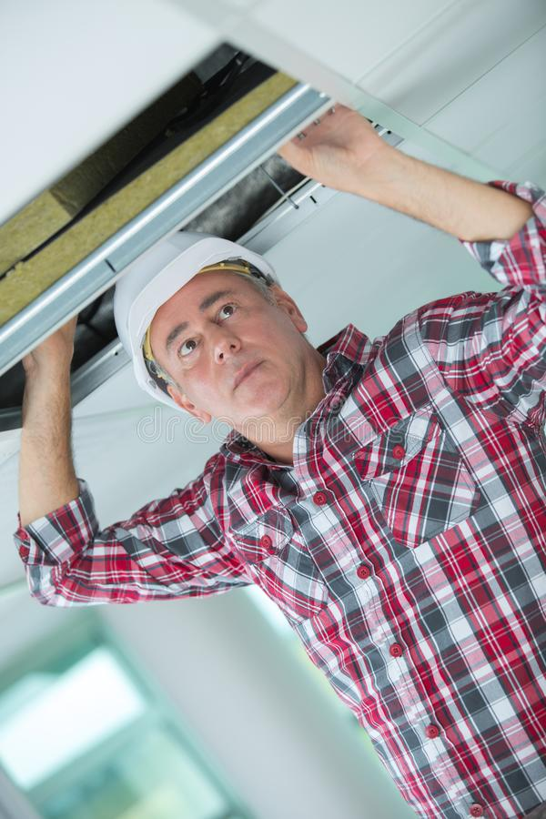 Handyman hiding cable in ceiling. Handyman hiding a cable in the ceiling royalty free stock photography
