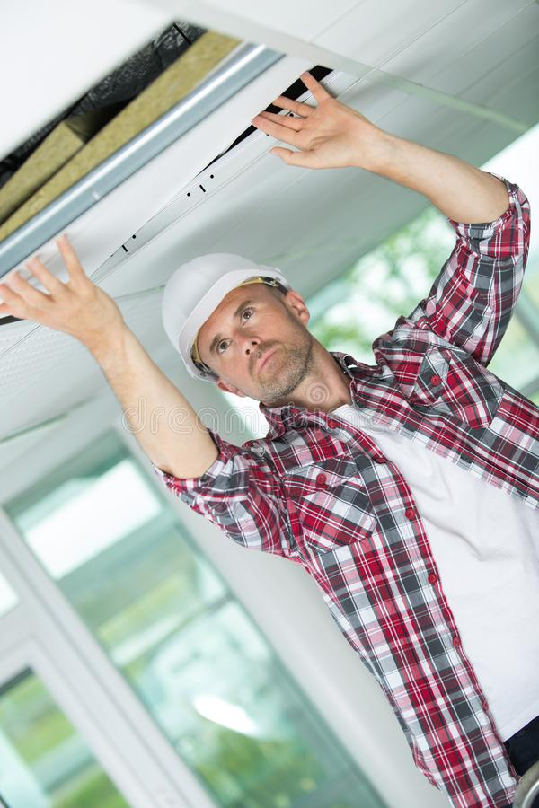 Handyman hiding cable with plinth. Handyman hiding a cable with a plinth stock image