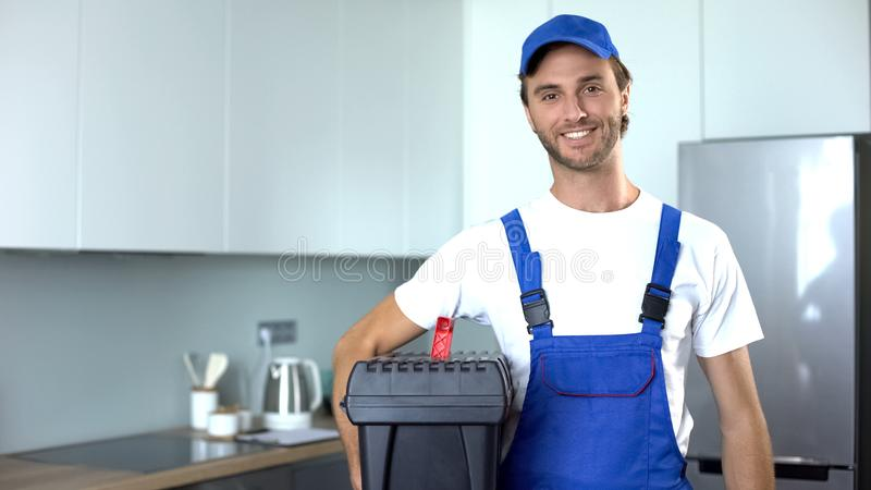Handyman holding tools standing in kitchen, professional plumbing services royalty free stock photos