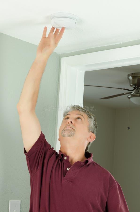 Handyman home owner checking smoke alarm testing. A handyman home owner is checking his house home smoke alarm by pushing the test button royalty free stock photo
