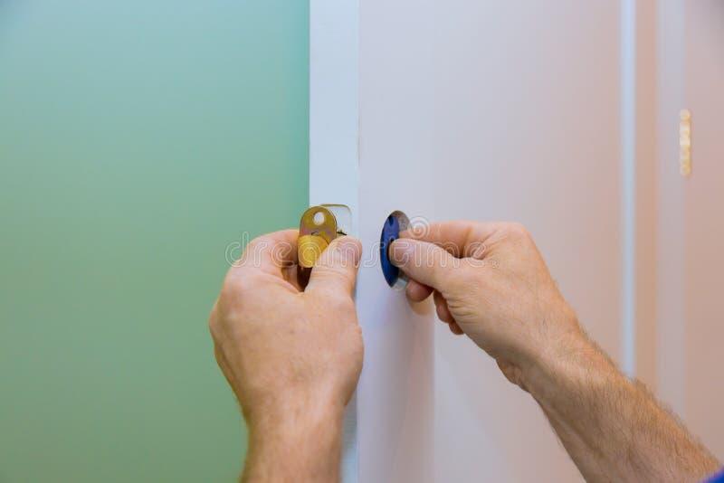 handyman installing the door lock in worker& x27;s hands installing new door locker stock photo