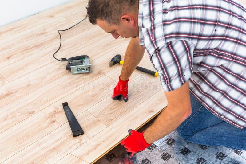 Handyman installing new laminated floor stock photo