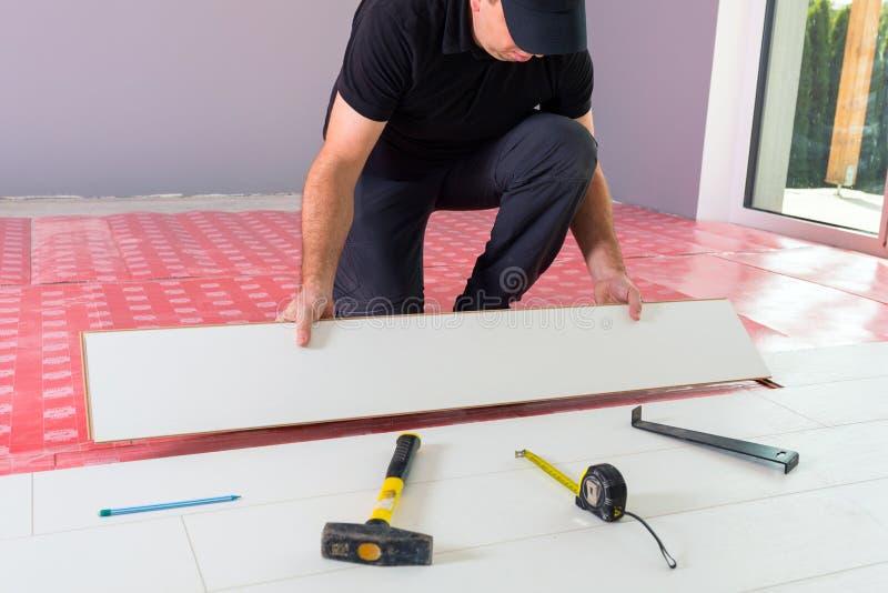 Handyman installing new laminated floor royalty free stock images