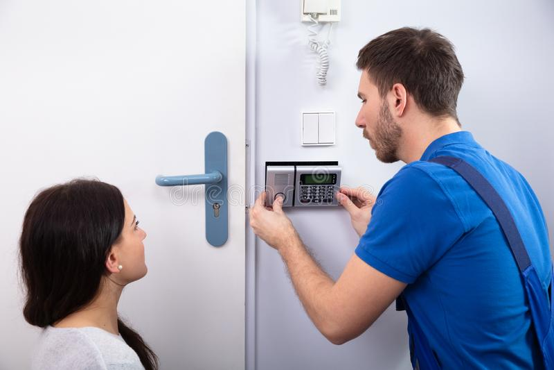 Handyman Installing Security System Near Door Wall. Close-up Of Handyman Installing Security System Near Door Wall While Woman Using Remote stock photos