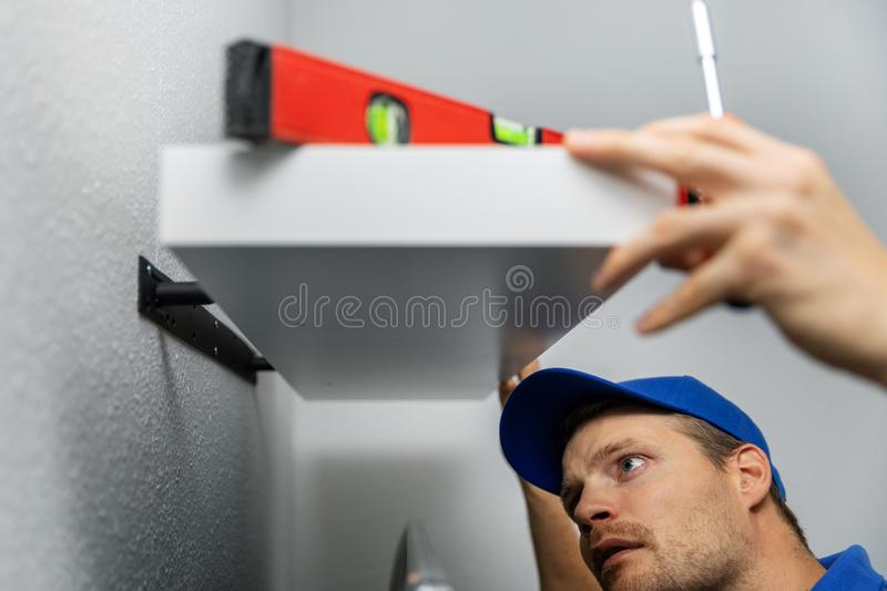 Handyman installing shelf on the wall at home stock photography
