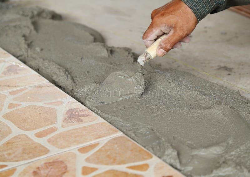 Handyman laying tile, trowel with mortar royalty free stock image