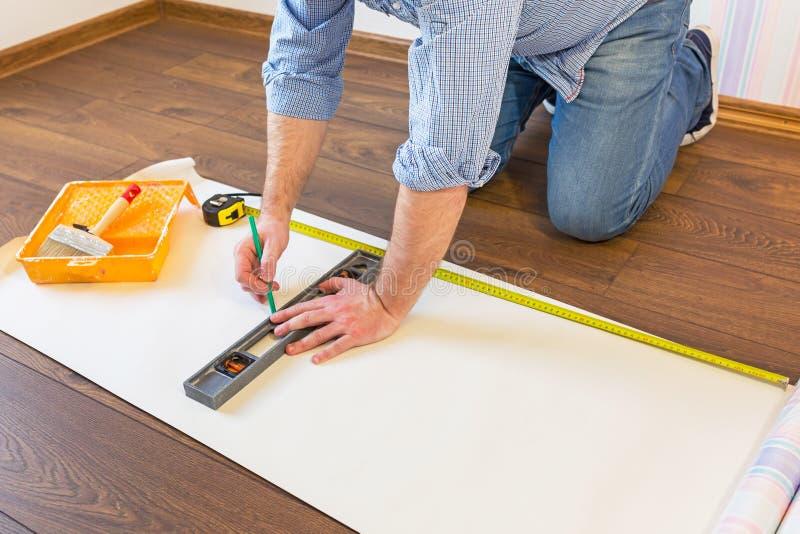Handyman measuring wallpaper to cut royalty free stock photography
