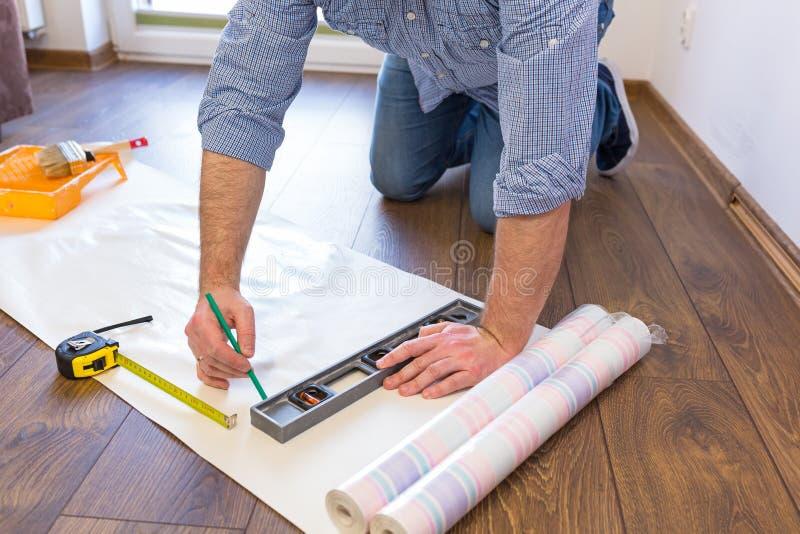 Handyman measuring wallpaper to cut royalty free stock image