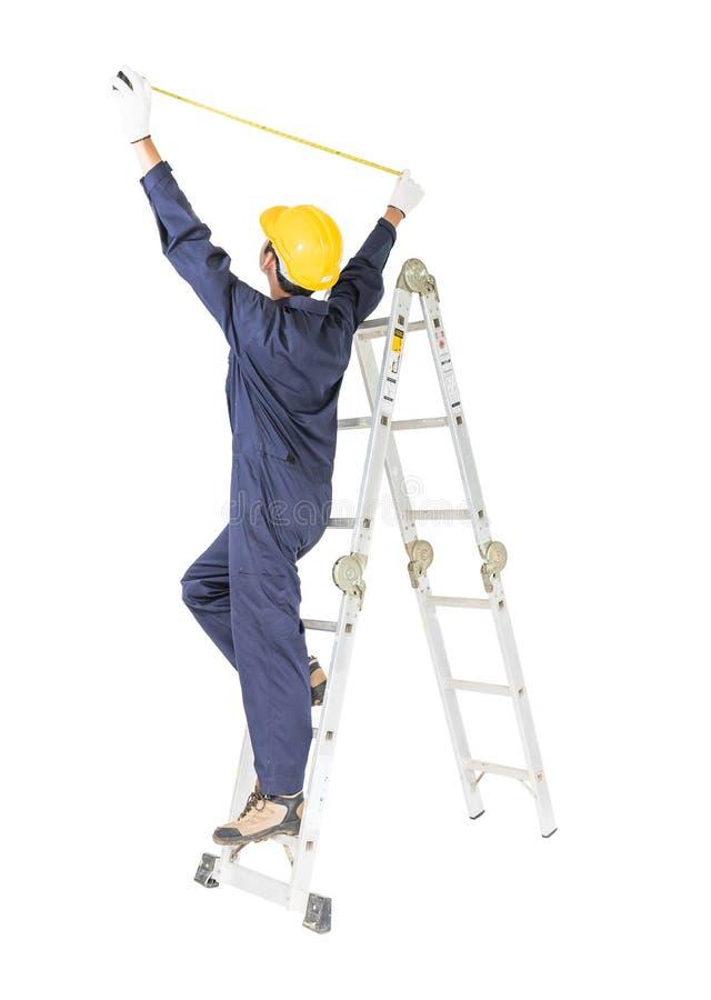 Handyman met uniforme positie op ladder bij gebruik van meetband op wit royalty-vrije stock foto