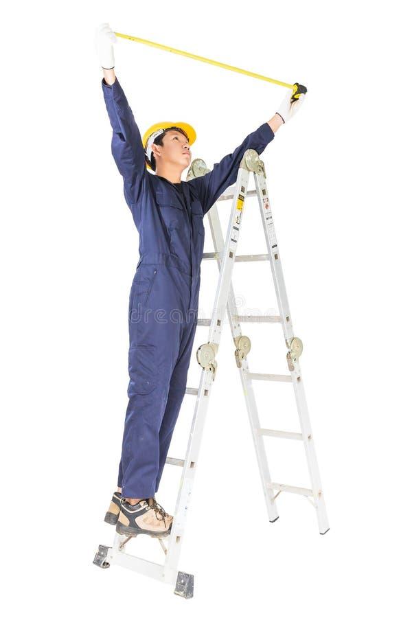 Handyman met uniforme positie op ladder bij gebruik van meetband op wit royalty-vrije stock afbeeldingen