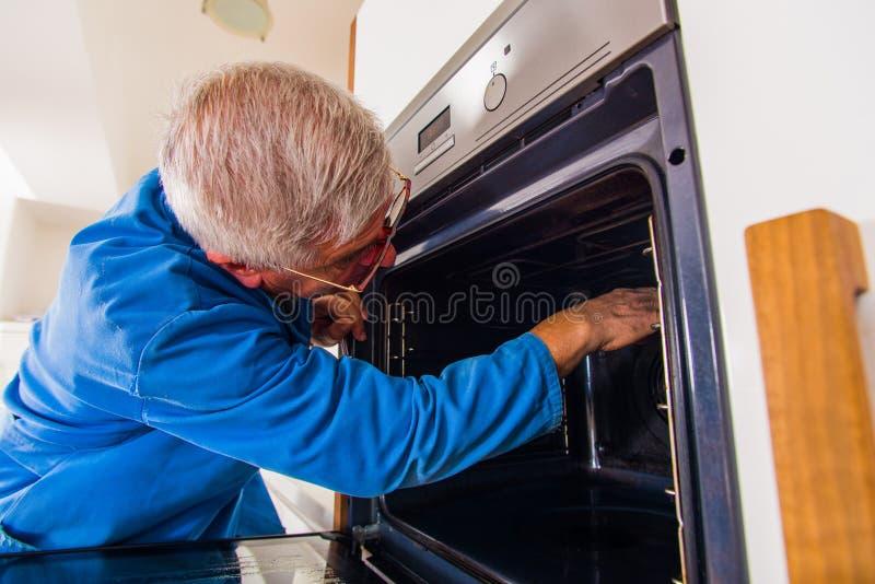 Handyman naprawia piekarnik zdjęcie royalty free