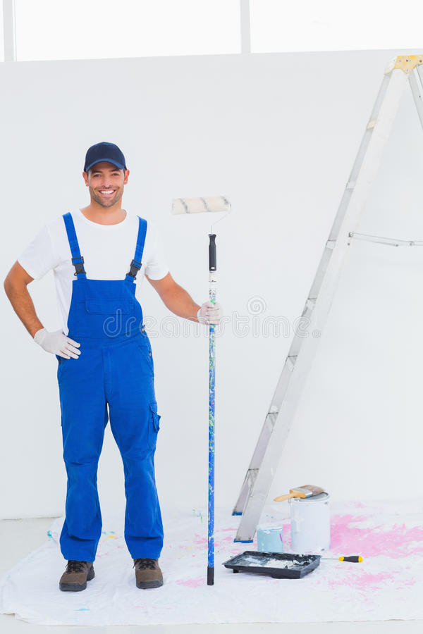 Handyman in overalls holding paint roller at home royalty free stock photos