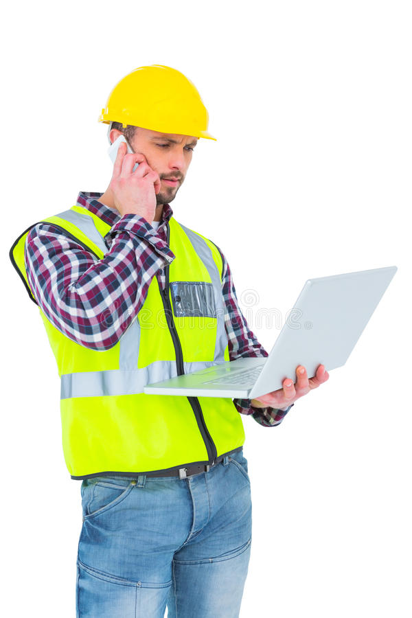 Handyman on the phone holding laptop. On white backboard stock images