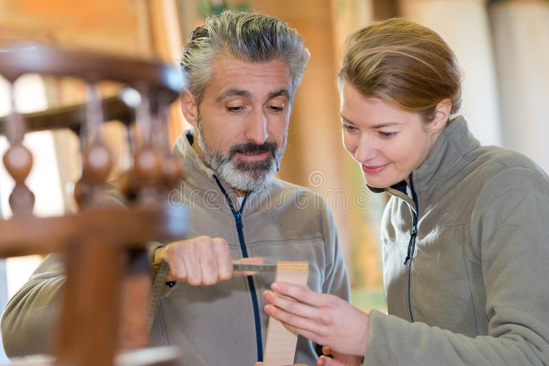 Handyman repairing furniture in kitchen. Handyman repairing furniture in the kitchen stock photo