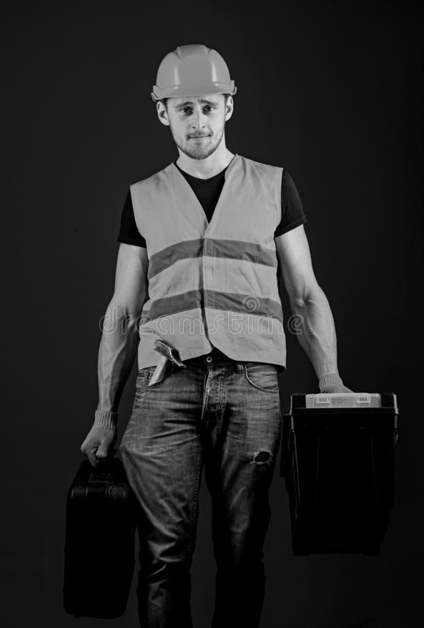 Handyman, repairman on strict face goes and carries bags with professional equipment. Professional repairman concept stock photo