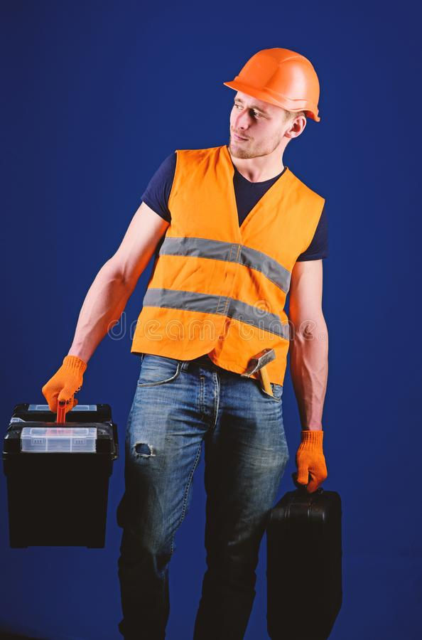 Handyman, repairman on strict face goes and carries bags with professional equipment. Man in helmet, hard hat holds royalty free stock photo
