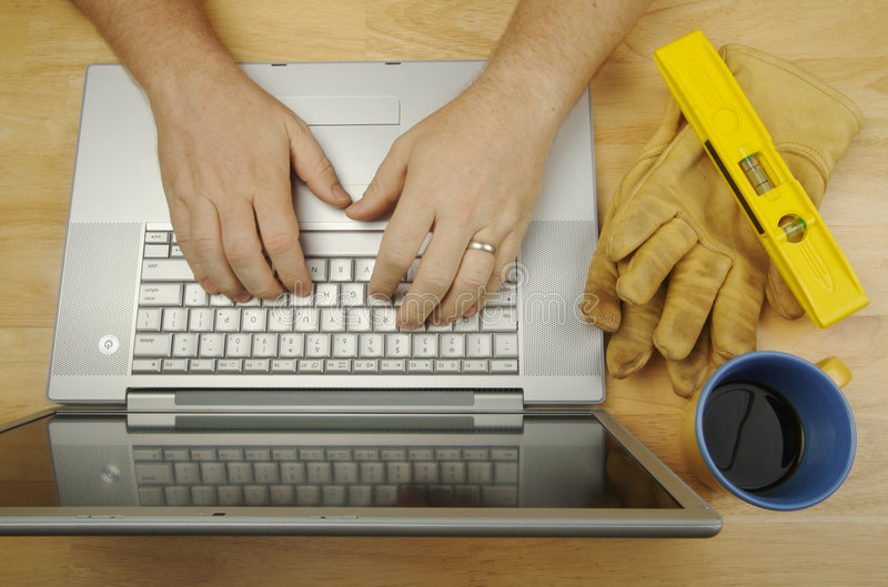 Handyman Researches on Laptop stock photos