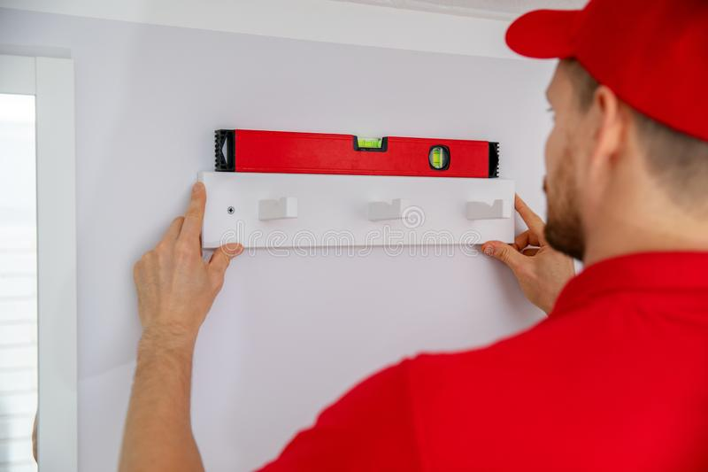 Handyman services - man installing towel hanger on the wall stock photography