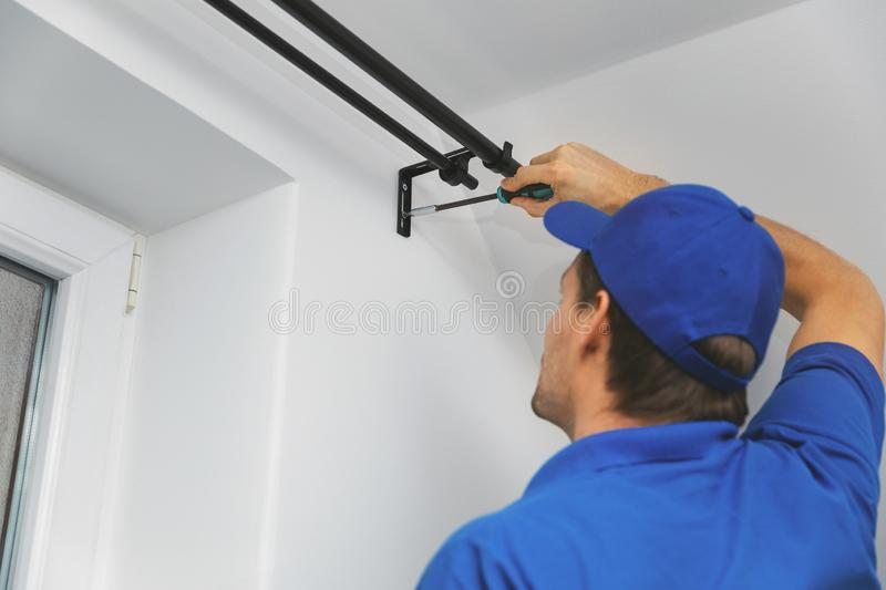 Handyman services - worker installing window curtain rod on the wall. At home royalty free stock photos