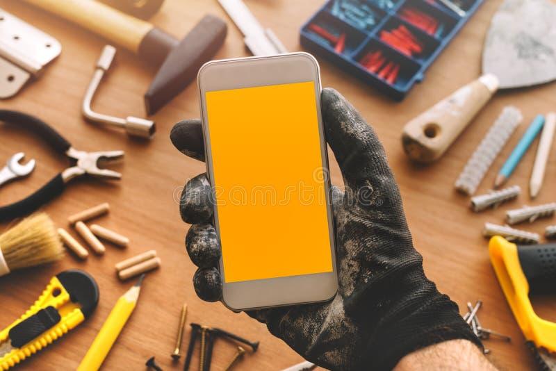 Handyman smart phone app, repairman holding mobile phone in hand royalty free stock photos