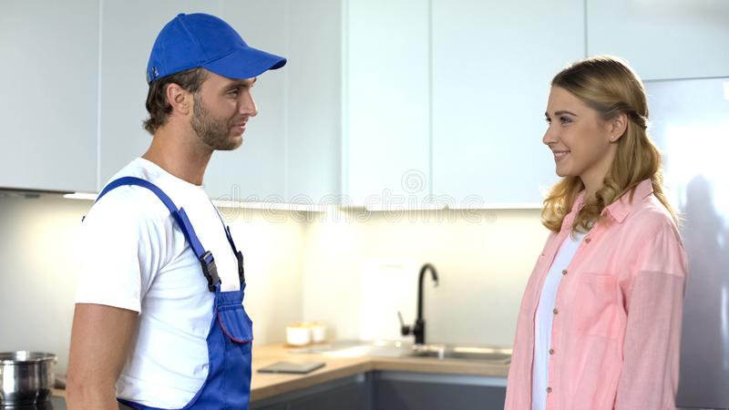 Handyman smiling to satisfied female client, professional repair services royalty free stock images