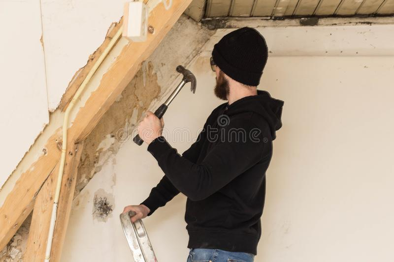 Handyman standing on a ladder and renovating a home, using tools like a hammer stock image