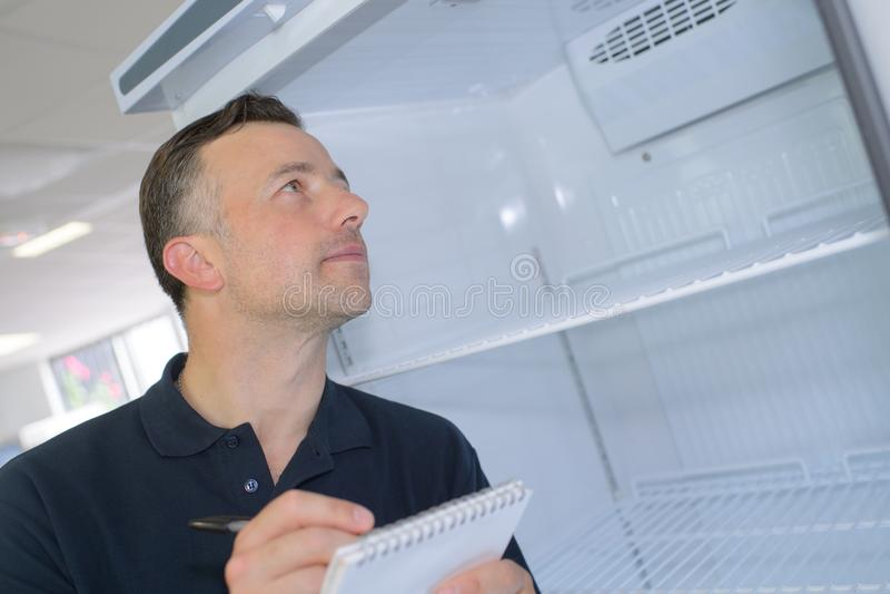 Handyman standing near fridge and taking notes stock photos