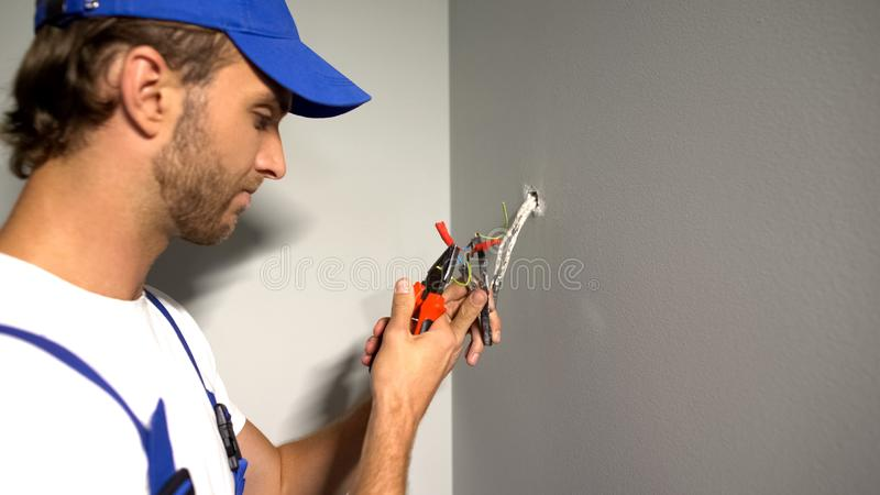 Handyman stripping wires, removing insulation with pliers, electrical services royalty free stock photography