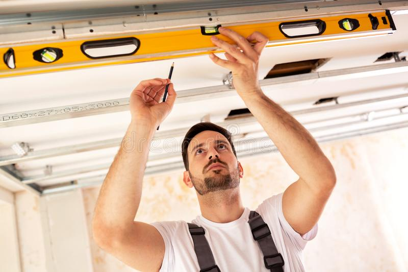 Handyman taking measures with spirit level stock images
