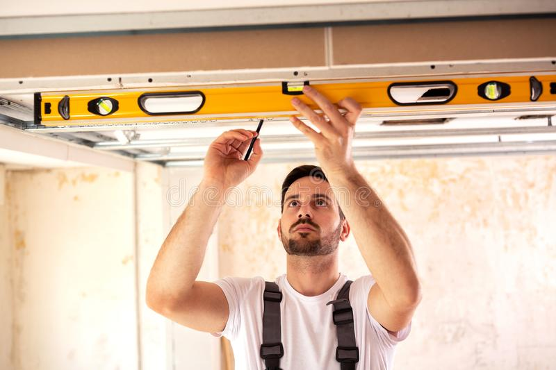 Handyman taking measures with spirit level stock photography