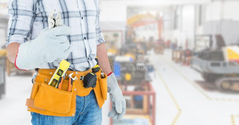 Handyman with tool belt at workshop. Mid section of handyman with tool belt at workshop royalty free stock images