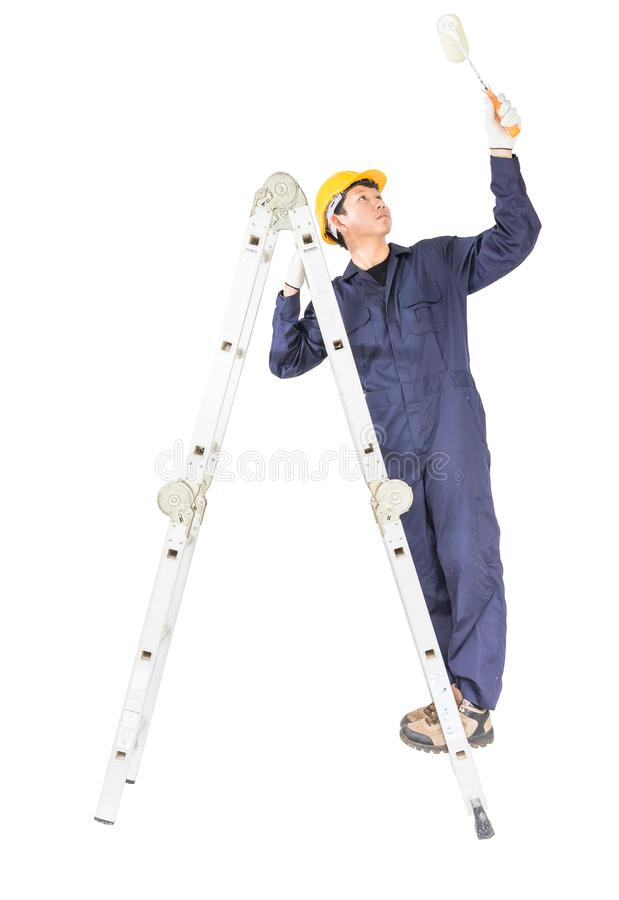Handyman in uniform standing on ladder while using paint roller stock photo