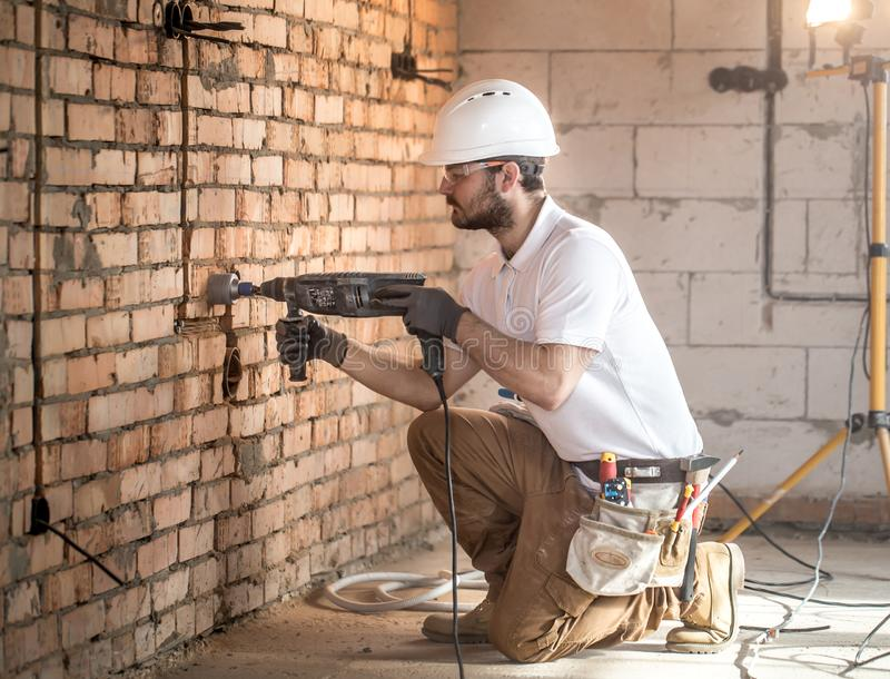 Handyman uses jackhammer, for installation, professional worker on the construction site. The concept of electrician and handyman royalty free stock image
