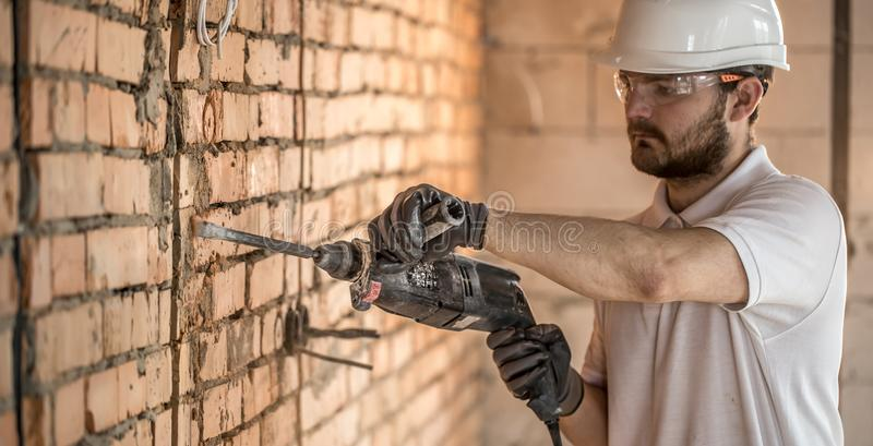 Handyman uses jackhammer, for installation, professional worker on the construction site. The concept of electrician and handyman stock photography