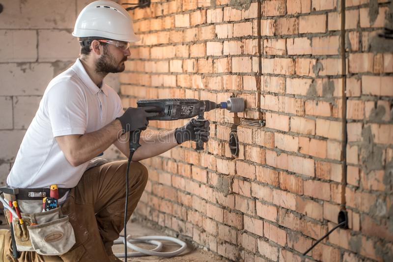 Handyman uses jackhammer, for installation, professional worker on the construction site. The concept of electrician and handyman royalty free stock photos