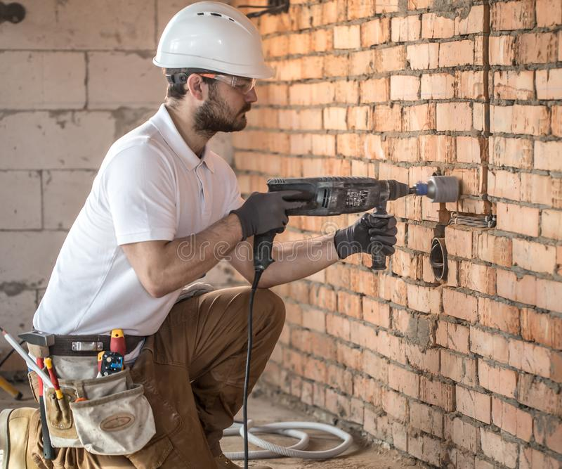 Handyman uses jackhammer, for installation, professional worker on the construction site. The concept of electrician and handyman royalty free stock images