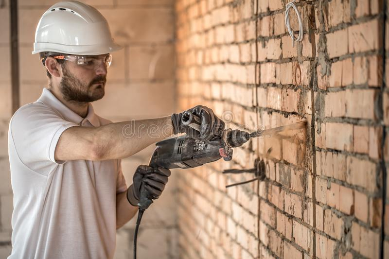 Handyman uses jackhammer, for installation, professional worker on the construction site. The concept of electrician and handyman stock photos