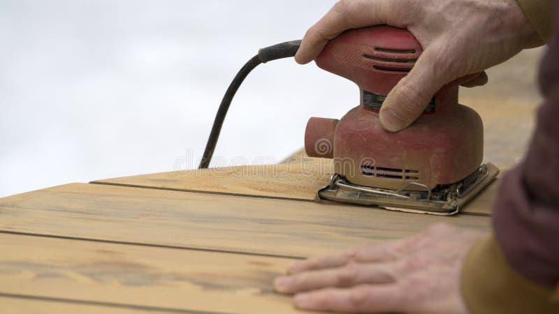 Handyman using Palm Sander on Cedar Table Top. Handyman uses a palm sander to refinish a red cedar outdoor patio table royalty free stock photography