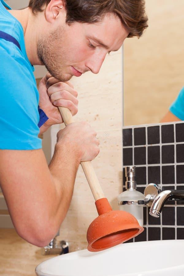 Handyman using plunger stock image