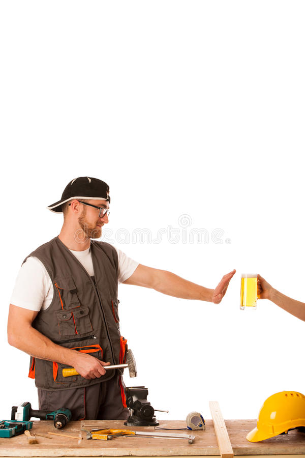 Handyman in work clothing refusing beer, don't drink on workplac royalty free stock image
