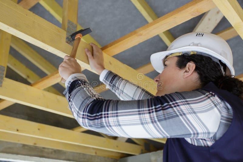 Handywoman hammering wood boards stock photos
