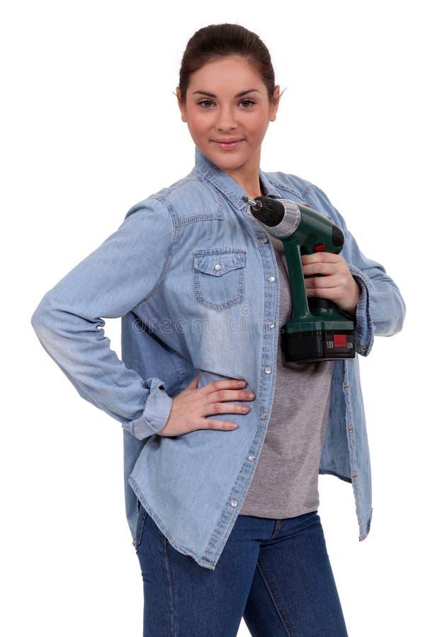 Handywoman posant avec le foret photographie stock