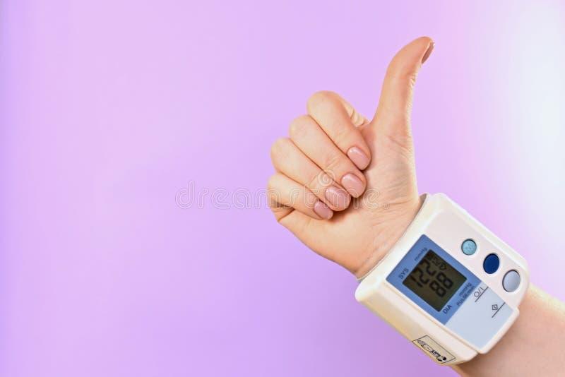 Handzeichen mit einem tonometer auf dem Handgelenk lizenzfreies stockbild