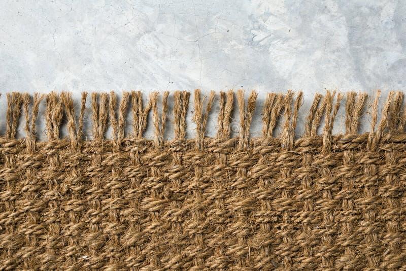 Hanfteppich auf Zementboden Sisalshintergrund oder -tapete lizenzfreies stockbild